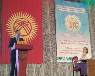 WONCA president speaking at family medicine congress in Bishkek, in front of the flag of Kyrgyzstan