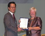 Host Organising Committee chair, Young Sik Kim receives presentation from Amanda Howe